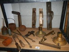 A shelf of assorted brass door handles and other architectural items.