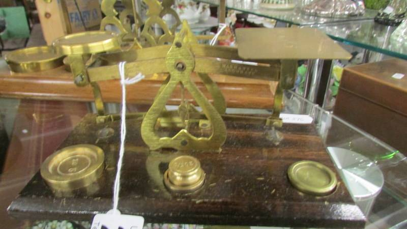 A set of brass postal scales with weights.