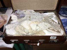 A small vintage case including vintage textiles,