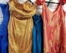 Four evening gowns in varying sizes and designs with lots of frills,