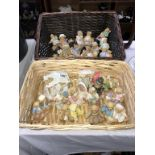 A collection of cherished teddies in 2 wicker baskets approximately 30 bears in total