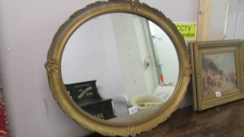 An oval gilt framed mirror.