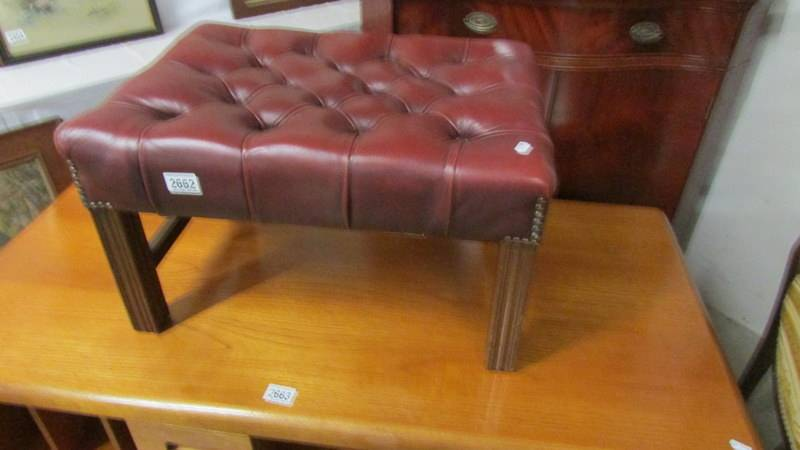 A good quality red leather foot stool.