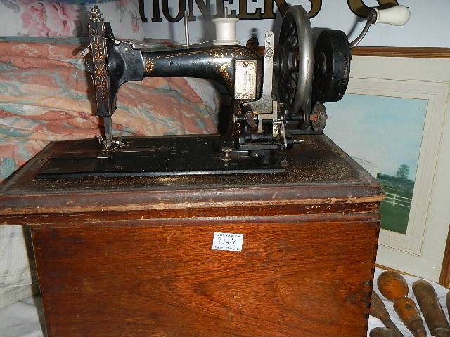 A hand operated sewing machine.