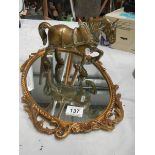 An oval cast mirror and a heavy cast brass horse.