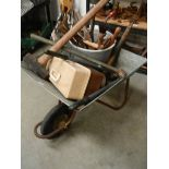 A galvanised wheel barrow with garden tools.