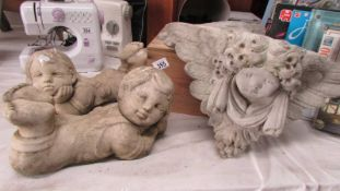 Two cherub garden ornaments and two others.