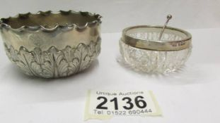 A small silver bowl and a silver rimmed salt with silver spoon.