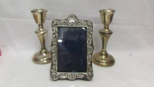 A pair of silver candlesticks, a/f and a silver photo frame also a/f.