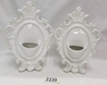 A pair of white ceramic pocket watch stands.