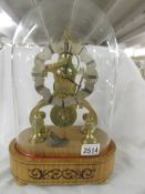 A good brass skeleton clock under glass dome.
