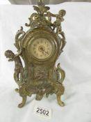 A heavy brass mantel clock surmounted cherubs.