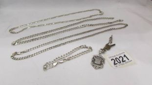 Three silver neck chains, a silver bracelet and a silver watch fob, approximately 75 grams.