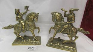 A pair of heavy brass horses with riders.