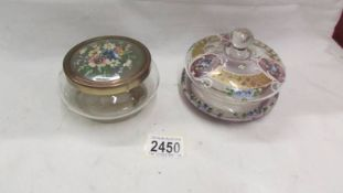 A decorative glass powder bowl and one other.