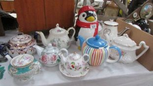 A Penguin biscuit jar and 8 assorted teapots.