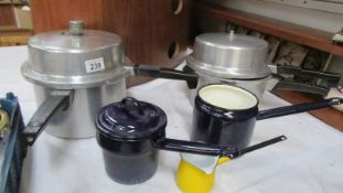 Two pressure cookers and three enamel pans.