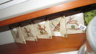 Five ceramic tiles depicting deer and one other.