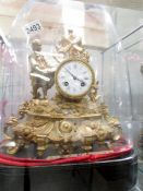 A French gilded mantel clock under glass dome.