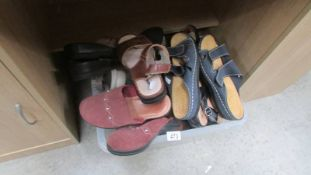 A box of assorted sandals and shoes.