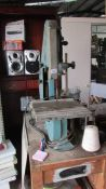 A bench bandsaw on bench with spare bands etc.