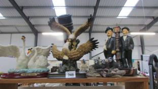 A selection of resin figures including swans, eagles, badgers and Laurel and Hardy.