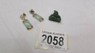 A pair of jade earrings and a jade Buddha pendant.