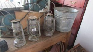 Three hurricane lamps and a galvanized bucket.