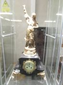 A 19th century French marble and gilt mantle clock with enamel dial and surmounted female figure.
