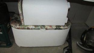 An ottoman and a linen bin.
