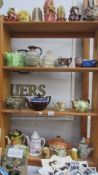 Four shelves of assorted teapots, candles etc.