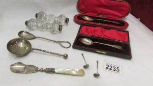 A collection of silver items including cased spoons, silver mounted knife rests etc.
