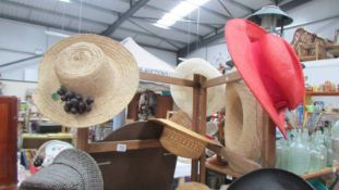 A collection of vintage hats and a wooden clothes horse.