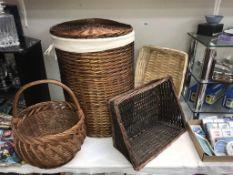 A wicker linen basket, shopping basket & 2 others.