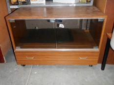 A TV cabinet with glazed doors.