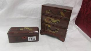 A miniature lacquered three drawer chest and a lacquered box.