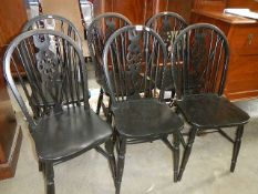 A set of 6 wheel back chairs.
