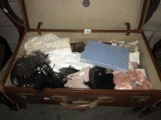 A large vinatge suitcase with vintage textiles including lace, ostrich feathers, handkerchiefs,