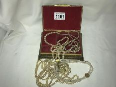A jewellery box containing pearl necklaces