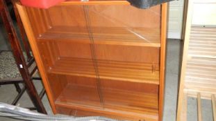 A 1960's book case with sliding glass doors.