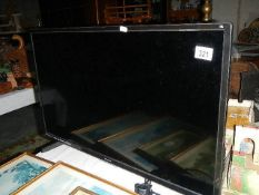 A Polaroid flat screen TV with remote.