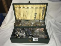 A green jewellery box with an assortment of costume jewellery