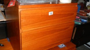 A teak two drawer chest.