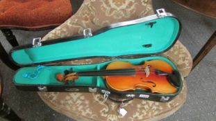 A cased three quarter size violin.