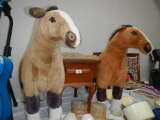 Two stuffed horses and a stool.