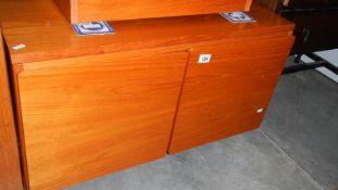 A teak two door cabinet.