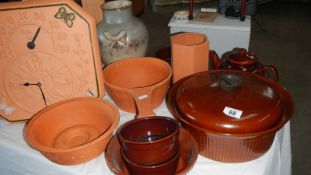 A quantity of brown pottery including wall clock.