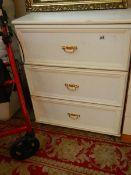 A white three drawer chest.