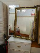 A gilt framed mirror and a white framed mirror.