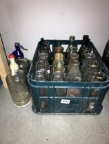 A plastic crate of vintage milk bottles and 2 soda syphons